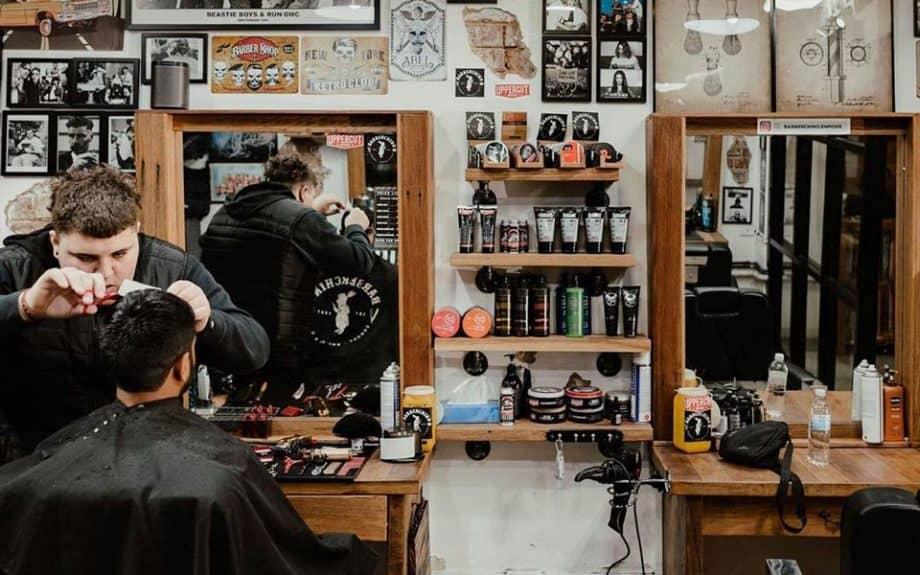 Barber cutting man's hair at Barberchino barber shop.