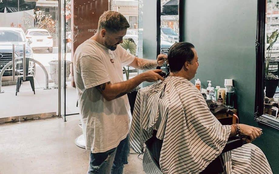 The Emporium Barber barber shop, barber cutting man's hair.