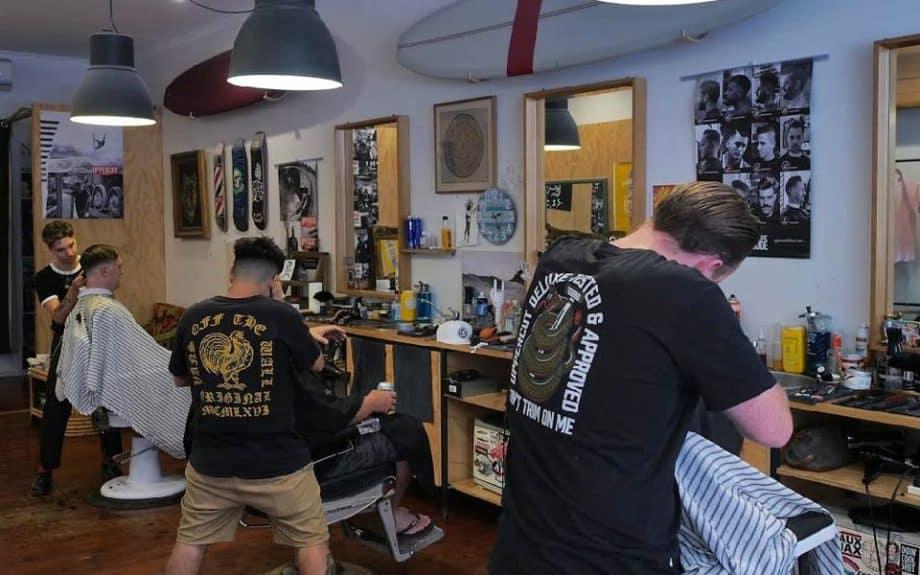 Three barbers cutting men's hair at Captain Sip Sop's barber shop, Sydney.