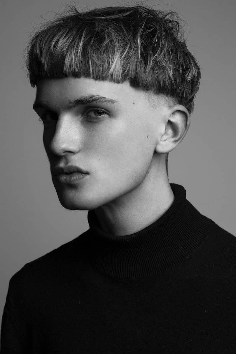 Man with bowl cut haircut, black and white.