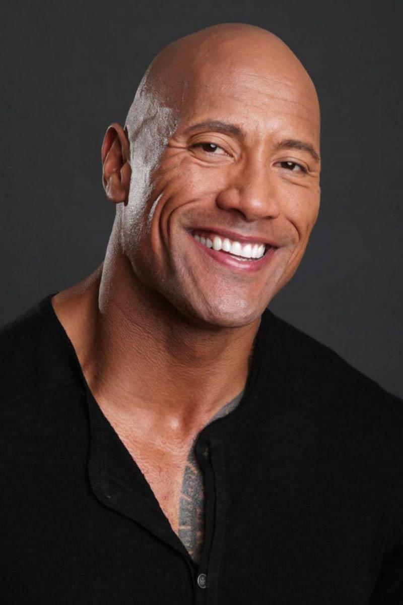 The Rock with no hair, smiling at camera.