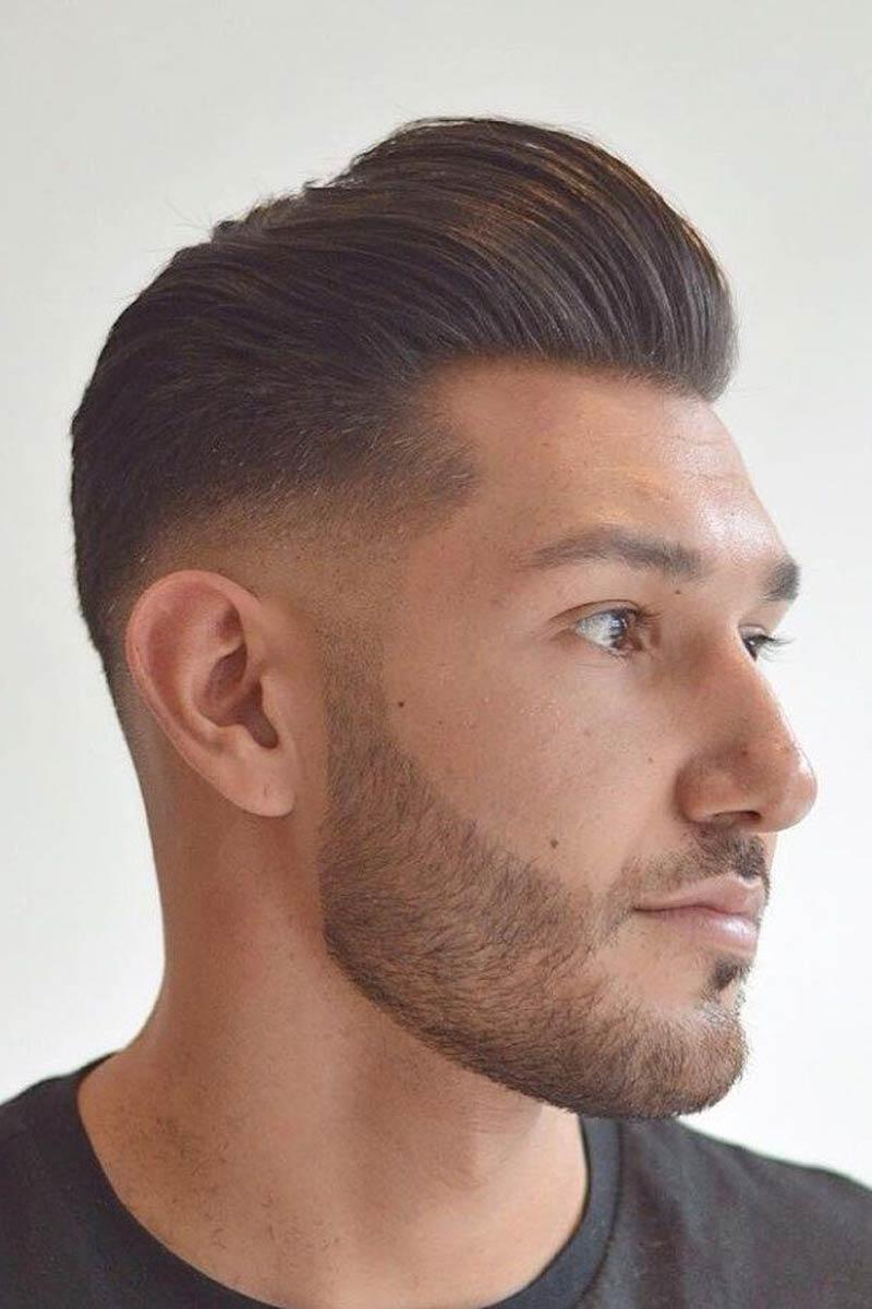 Man with facial hair and short pompadour haircut.