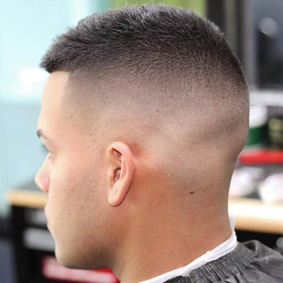 Rear view of man's head with high fade and buzz cut.