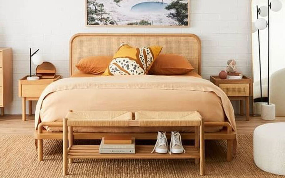 Large Life Interiors bed with coral and orange-coloured bedding. Wooden shoe rack at bottom of bed.